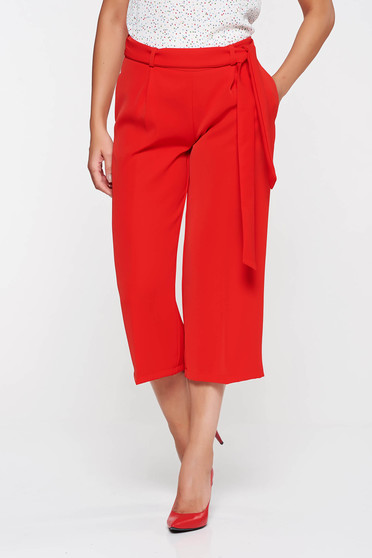 PrettyGirl red high waisted flaring cut trousers accessorized with tied waistband