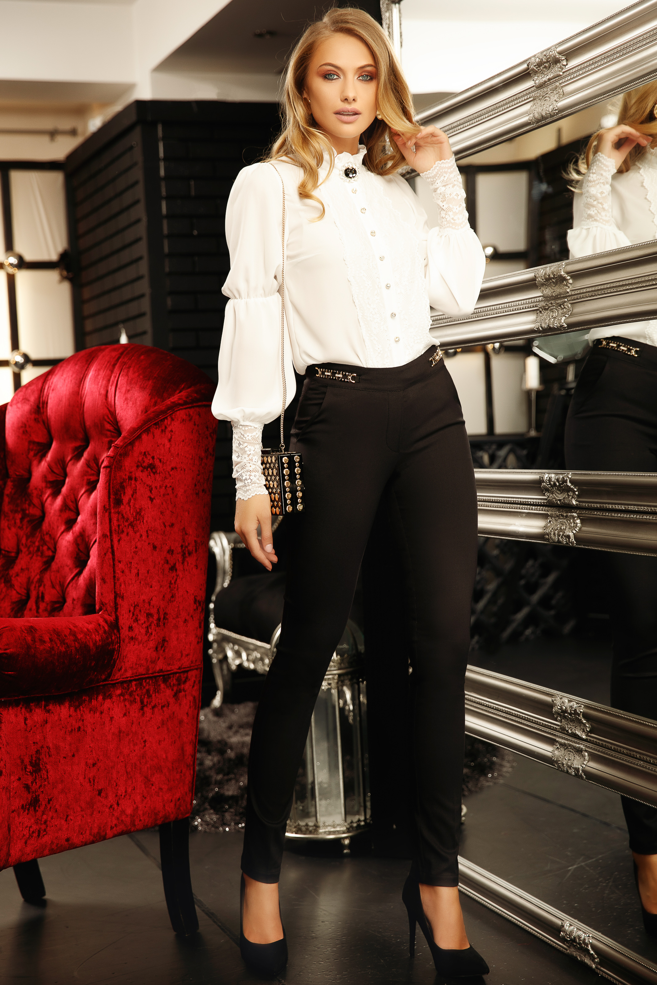 Elegant women`s shirt with easy cut from veil fabric with lace details accessorized with breastpin white