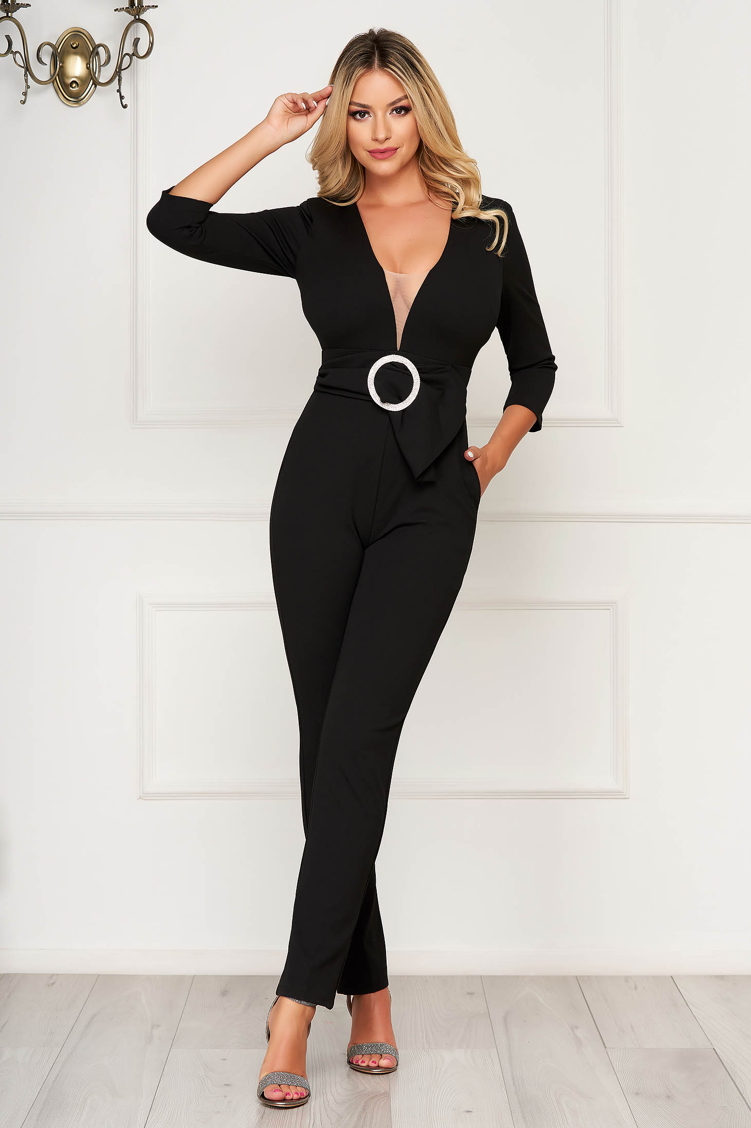 Jumpsuit black occasional with deep cleavage with v-neckline with 3/4 sleeves accessorized with breastpin