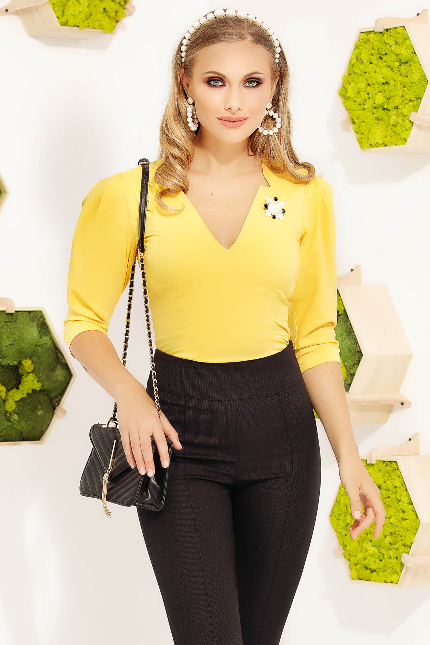 Women`s shirt yellow elegant accessorized with breastpin with v-neckline with puffed sleeves