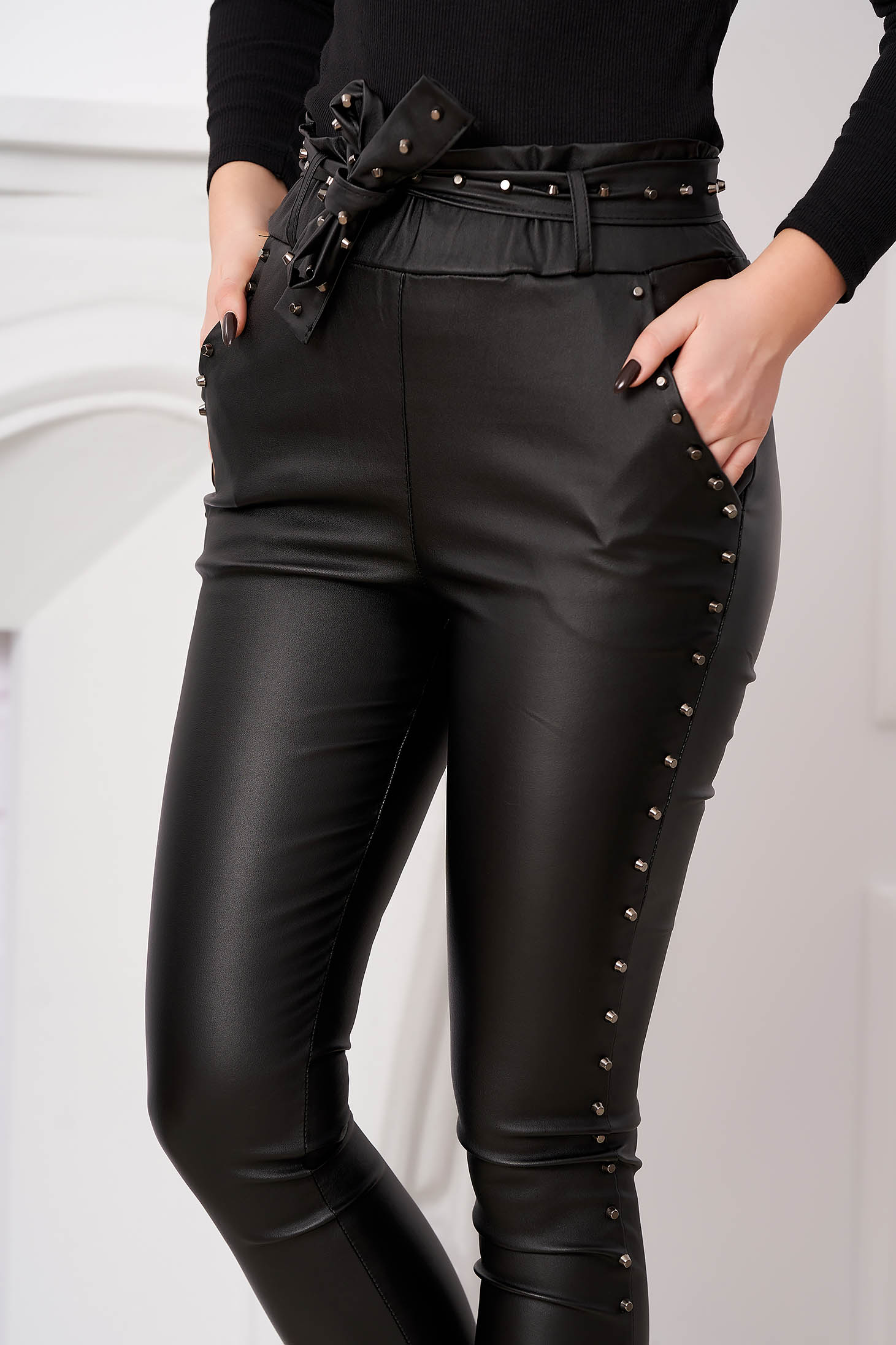 Black trousers with metallic spikes from ecological leather high waisted with tented cut