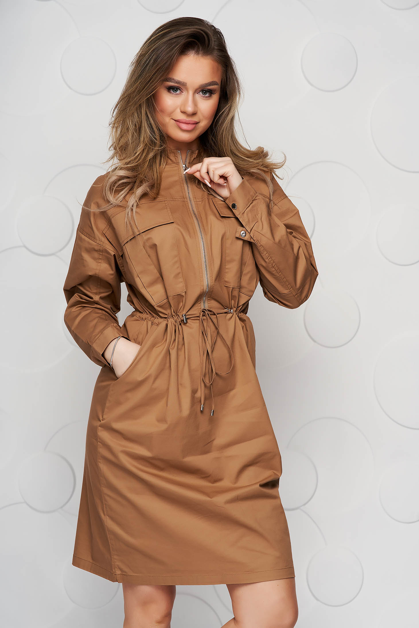 Lightbrown dress short cut straight long sleeved is fastened around the waist with a ribbon