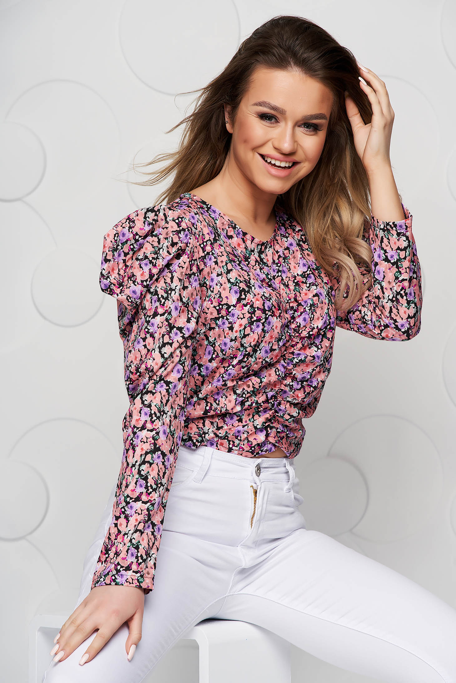 Pink women`s blouse with floral print tented from wrinkled fabric high shoulders