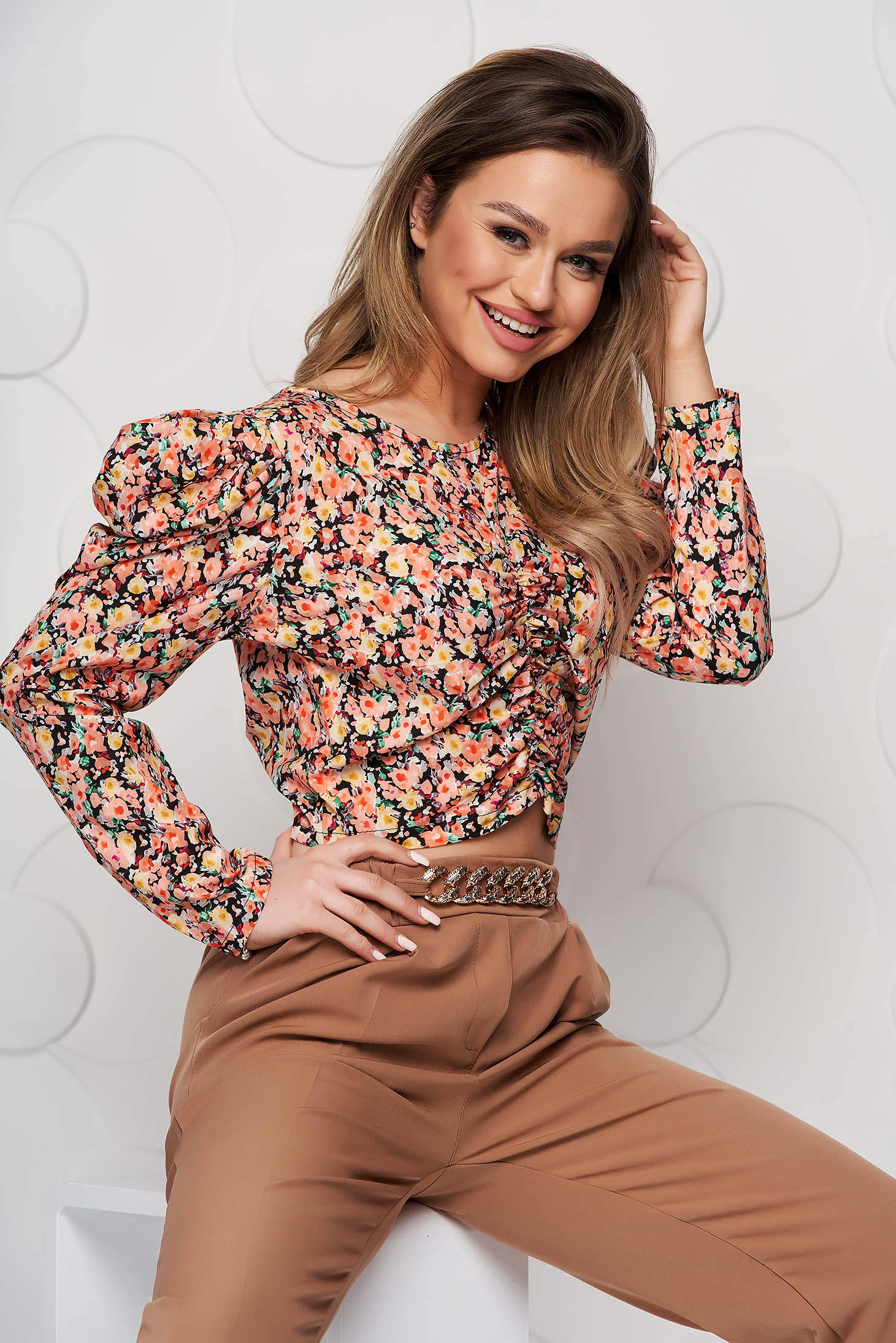 Orange women`s blouse with floral print tented from wrinkled fabric high shoulders