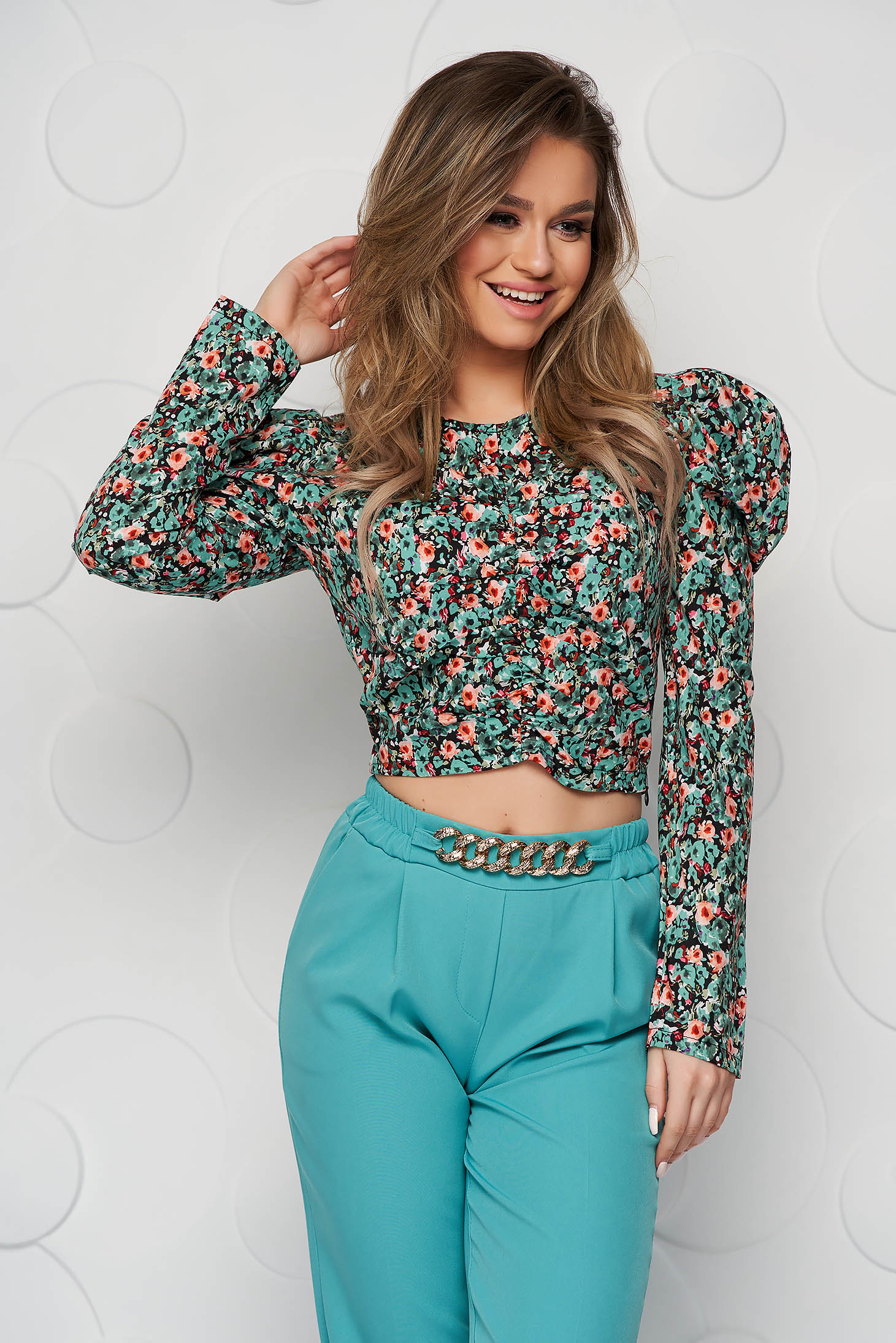 Darkgreen women`s blouse with floral print tented from wrinkled fabric high shoulders