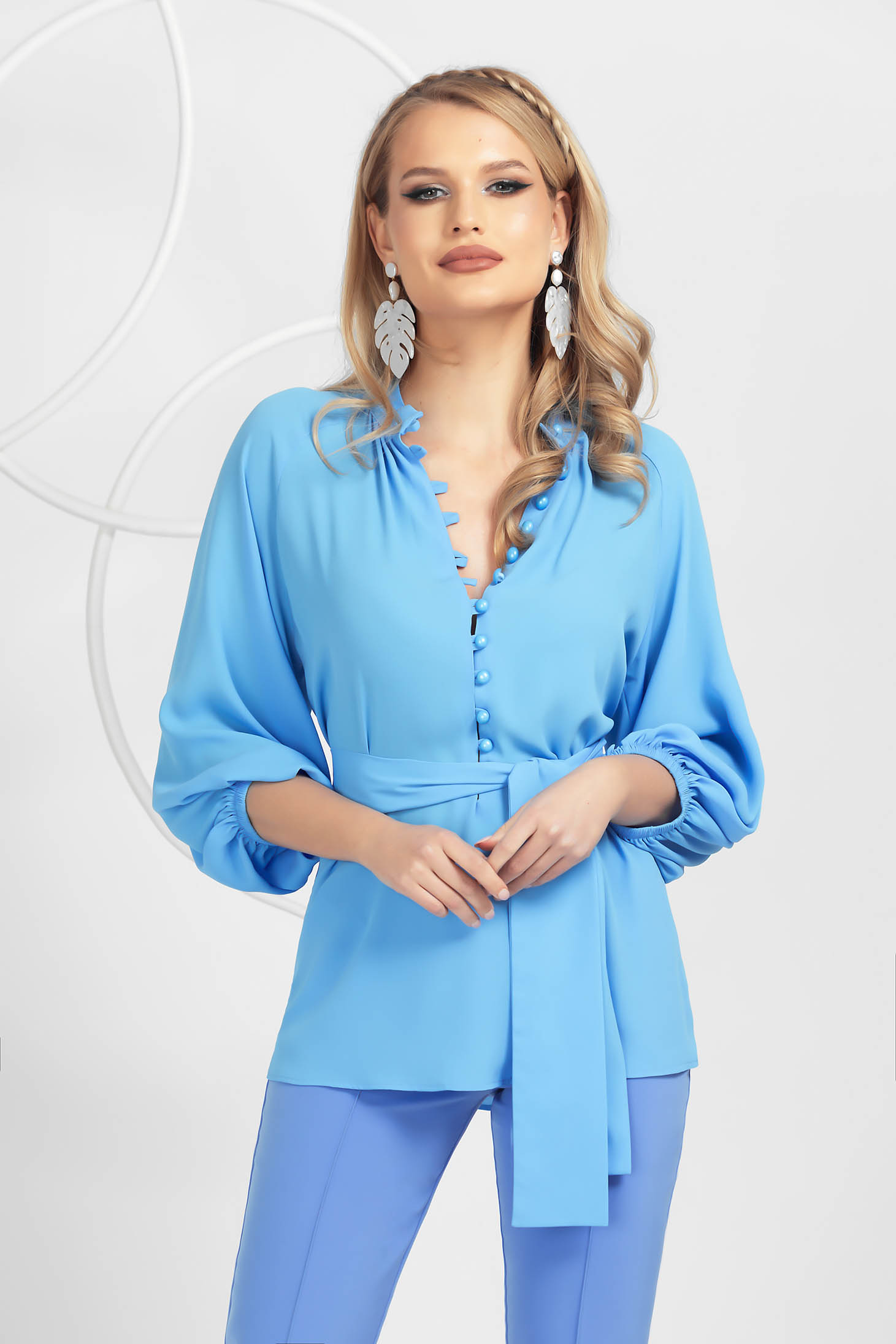 Lightblue women`s blouse from veil fabric accessorized with tied waistband with button accessories with puffed sleeves